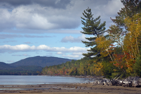 county somerset: Colorful fall foliage on shoreline of Flagstaff Lake in northwestern Maine, with mountains in the background, open water and partly cloudy skies. Stock Photo