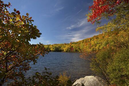 red maples: Dramatic fall foliage of red maples and yellow birches along shore of Russell Pond in the White Mountains near Woodstock, New Hampshire, horizontal image. Stock Photo