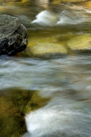 turbulence: Gentle flow of the Sugar River in Newport, New Hampshire, with silky turbulence near an exposed rock.