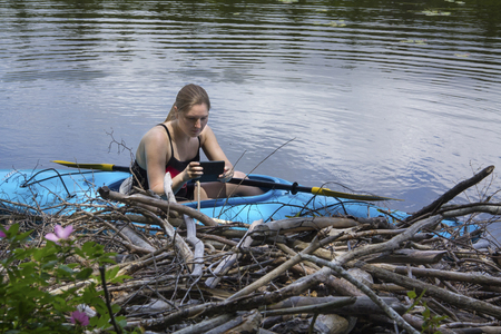 facing right: Young woman in blue kayak, facing right while using a cell phone to photograph a beaver lodge on Mud Pond in Sunapee, New Hampshire, on a sunny day, closeup, horizontal image. Stock Photo