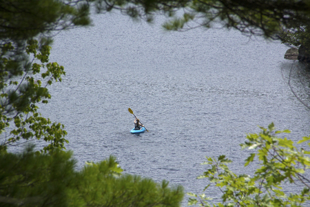 Young woman in blue kayak, paddling away from camera, on Mud Pond in Sunapee, New Hampshire, on a sunny day, framed by tree branches, horizontal image. Фото со стока
