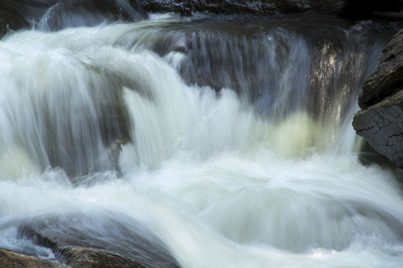 obody: Small waterfall in the Sugar River, Newport, New Hampshire, with heavy current, rocks and silky turbulence, horizontal.
