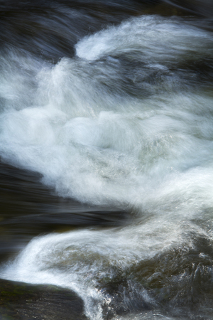 splash of water: Small rapids and silky turbulence of whitewater over rocks of the Sugar River, Newport, New Hampshire, vertical.