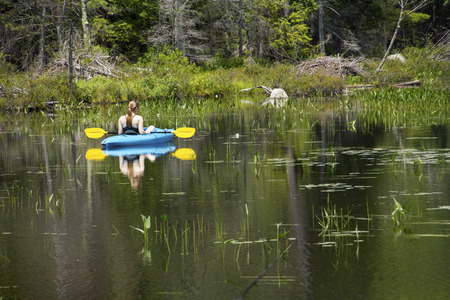 facing away: Young woman in blue kayak, coasting right in middle distance on Mud Pond in Sunapee, New Hampshire, on a sunny day, horizontal image. Stock Photo