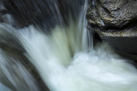 turbulence: Small waterfall in the Sugar River, Newport, New Hampshire, with rocks and silky turbulence, closeup.