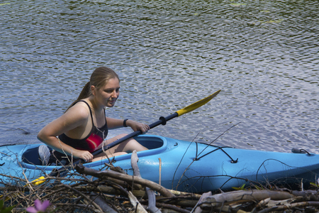 facing right: Young woman in blue kayak, stopped, facing right while observing a beaver lodge on Mud Pond in Sunapee, New Hampshire, on a sunny day, closeup, horizontal image.
