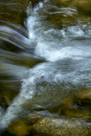 Gentle flow of the Sugar River in Newport, New Hampshire, with a small rapids and silky turbulence in a closeup.