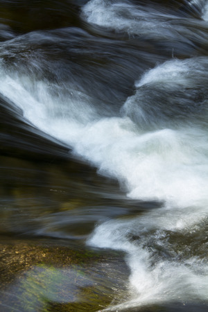 turbulence: Small rapids and silky turbulence of whitewater over rocks of the Sugar River, Newport, New Hampshire, vertical.