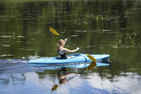 facing right: Young woman in blue kayak, paddling hard right, creating a wake on Mud Pond in Sunapee, New Hampshire, on a sunny day, horizontal image. Stock Photo
