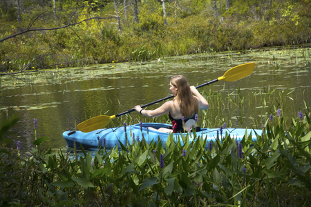 pickerel: Young woman in blue kayak, paddling left closeup through pickerel week flowers on Mud Pond in Sunapee, New Hampshire, on a sunny day, horizontal image. Stock Photo