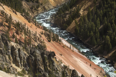 igneous: Steep and deep ravine of the Grand Canyon of the Yellowstone River, with yellow and pink cliffs, green pines, and rapids in the river below.