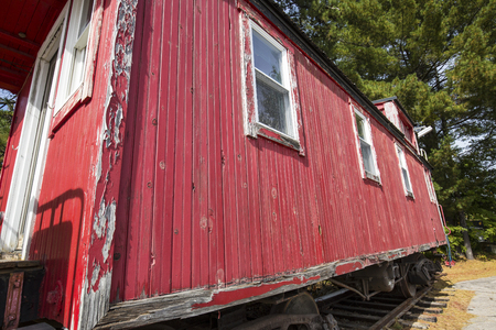 caboose: Side of red caboose parked on rails in North Conway, New Hampshire.