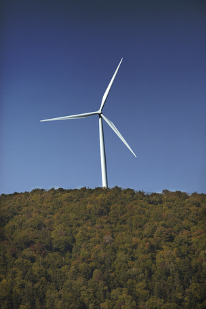 pollution free: Closeup view of a windfarm, showing a single white windmill on a high ridge with a blue sky on a sunny day in northern Maine, near Roxbury.