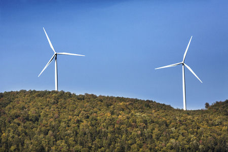 pollution free: View of a windfarm, showing 2 windmills on a high ridge with a blue sky on a sunny day in northern Maine, near Roxbury. Stock Photo