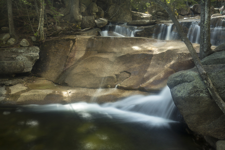 bedrock: Double waterfall of Lucy Brook, with long exposure, over granite bedrock at Dianas Baths in Bartlett, New Hampshire.