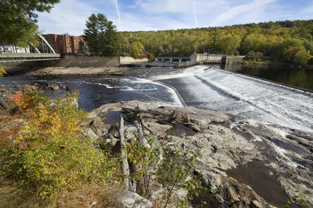 Water flows over a dam on the Androscoggin River at Rumford, Maine on a sunny day in October.