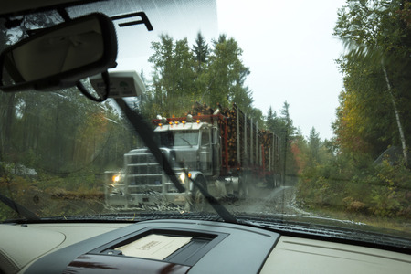logging truck: Perilous encounter with a logging truck taking most of a muddy dirt road, in the rain in the Great North Woods near Rangeley, Maine.