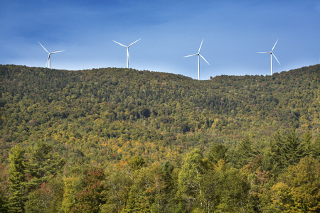 pollution free: View of a windfarm with 4 windmills on a high ridge with a blue sky on a sunny day in northern Maine, near Roxbury. Stock Photo