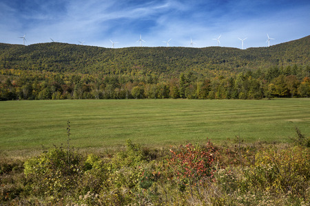 pollution free: View of a windfarm with ten windmills on a high ridge above green grass of a pasture, with fall foliage and a blue sky on a sunny day in northern Maine, near Roxbury. Stock Photo