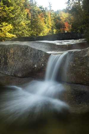 ledge: Fall foliage with long exposure of waterfall over granite ledge at Dianas Baths near North Conway, New Hampshire.
