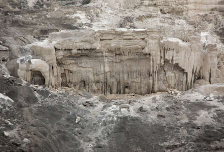 the deposits: Gray lime deposits resembling a dystopian hideout in cliffs of hot springs in Yellowstone National Park, Wyoming. Stock Photo