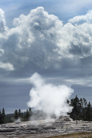 dark clouds: Old Faithful Geyser steaming in Upper Geyser Basin of Yellowstone National Park, Wyoming, with big, dark clouds in the sky.