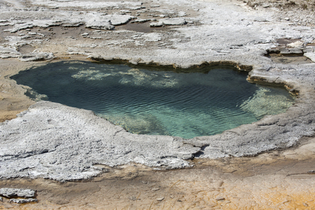 thermal spring: Aqua water in hot spring pool with limestone rock border at Mammoth Hot Springs in Yellowstone National Park, Wyoming.