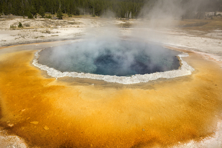 hydrothermal: Morning Glory Pool, a hot spring in Upper Geyser Basin of Yellowstone National Park, Wyoming, with steaming water and a white limestone rim.