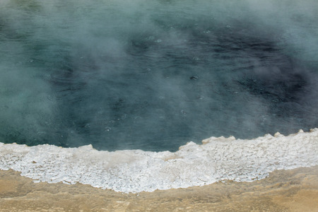 hydrothermal: Steaming, bubbling, aqua water of Morning Glory Pool, a hot spring in Upper Geyser Basin of Yellowstone National Park, Wyoming, with a white limestone rim. Stock Photo