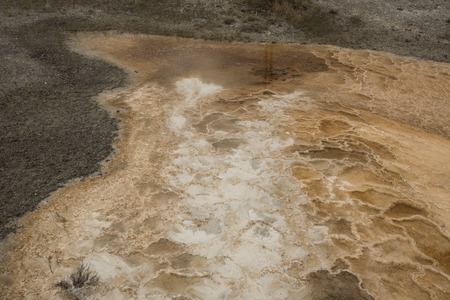 hydrothermal: Colorful, orange geothermal streams and pools of hot water with white carbonate deposits and ridges, overlying the travertine rock of Mammoth Hot Springs in Yellowstone National Park, Wyoming. Stock Photo