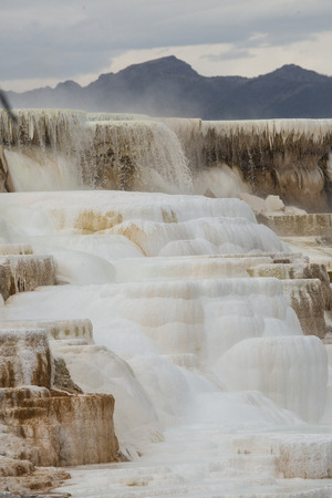 hydrothermal: Geothermal flow of hot, carbonate rich water, forms cascading, dark orange travertine terraces, with steam rising and mountains in the background, at Mammoth Hot Springs in Yellowstone National Park, Wyoming. Stock Photo