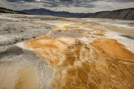 hot water geothermal: Colorful, orange geothermal pool of hot water overlying travertine rock, with mountains in the background at Mammoth Hot Springs in Yellowstone National Park, Wyoming. Stock Photo