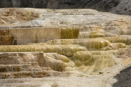 hot water geothermal: Geothermal flow of hot, carbonate rich water, forms orange travertine terraces at Mammoth Hot Springs in Yellowstone National Park, Wyoming. Stock Photo