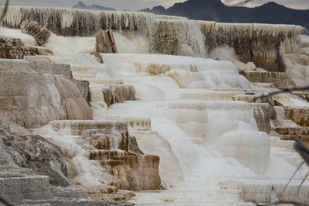 hot water geothermal: Geothermal flow of hot, carbonate rich water, forms cascading, dark orange travertine terraces, with mountains in the background, at Mammoth Hot Springs in Yellowstone National Park, Wyoming.