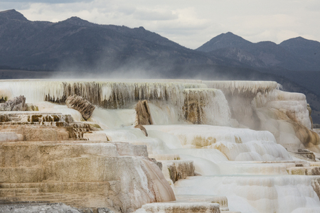 thermal spring: Geothermal flow of hot, carbonate rich water, forms cascading, dark orange travertine terraces, with steam rising and mountains in the background, at Mammoth Hot Springs in Yellowstone National Park, Wyoming. Stock Photo