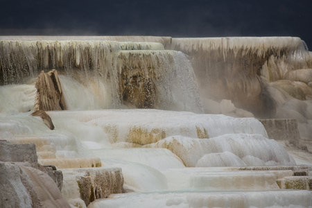 hot water geothermal: Geothermal flow of hot, carbonate rich water, forms cascading, dark orange travertine terraces, with steam rising at Mammoth Hot Springs in Yellowstone National Park, Wyoming. Stock Photo