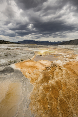 thermal spring: Colorful, orange geothermal pool of hot water overlying travertine rock, with mountains in the background and dark clouds overhead at Mammoth Hot Springs in Yellowstone National Park, Wyoming.