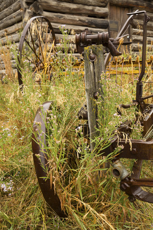 farm implements: Antique, rusting metal farm implements in front of log cabin, Jackson, Wyoming, on a rainy summer day.