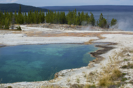 microbial: Blue water with orange microbial mats, steam and white lime of a hot springs in the West Thumb basin, Yellowstone National Park, Wyoming. Yellowstone Lake is in the background.