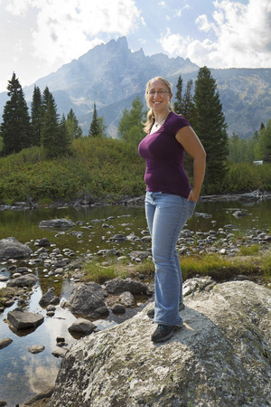 rock creek: Young woman with plain purple top and jeans, hand in back pockets, standing on a rock in Cottonwood Creek, with the Teton Mountains in the background, Wyoming. Stock Photo