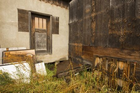 plaster board: Elevated brown door and dark brown plywood siding of old building in disrepair, with boards leaning against a tan plaster wall, Jackson, Wyoming.