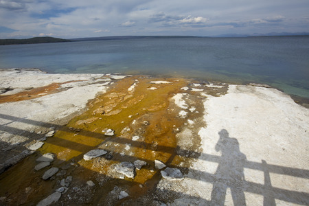 runoff: Orange surface runoff and lime crust on the shore of Yellowstone Lake, with self-portrait shadow of the photographer on a boardwalk, in the West Thumb basin of Yellowstone National Park, Wyoming.