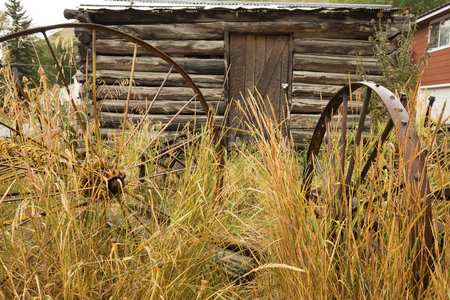 farm implements: Antique, rusting metal farm implements in the grass directly in front of log cabin, Jackson, Wyoming, on a rainy summer day. Stock Photo