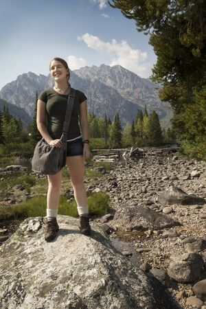 rock creek: Young woman with hands at her sides, standing on a rock in Cottonwood Creek, with  the Teton Mountains in the background, Wyoming.