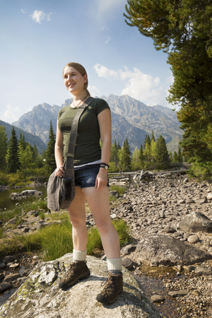 Young woman with hands at her sides, standing on a rock in Cottonwood Creek, facing left, with the Teton Mountains in the background, Wyoming. Stock Photo