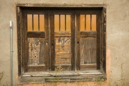jackson: Three old brown doors, each with three orange windows, in tan plaster wall, Jackson, Wyoming.