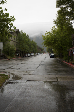 Ski Area: Looking down Millward Street to Snow King ski area, downtown Jackson, Wyoming, on a rainy summer day, with shiny wet roads, vertical image.
