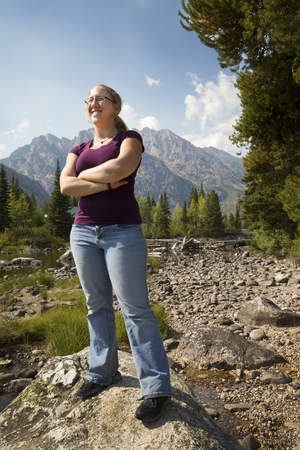 rock creek: Young woman with plain purple top and jeans, standing on a rock in Cottonwood Creek, arms crossed, with the Teton Mountains in the background, Wyoming.