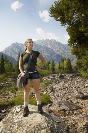 rock creek: Young woman with hand on hip, standing on a rock in Cottonwood Creek, looking up to the right, with the Teton Mountains in the background, Wyoming.