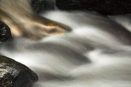 Small rapids, with gold tongue, in the Sugar River, Newport, New Hampshire. Long exposure, horizontal image. Stock Photo